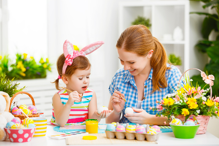 gelukkig gezin moeder en kind meisje schildert eieren voor Pasen thuis Stockfoto