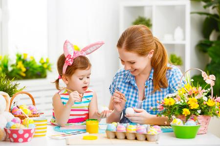 madre de familia feliz y chica niño pinta los huevos de Pascua en el hogar