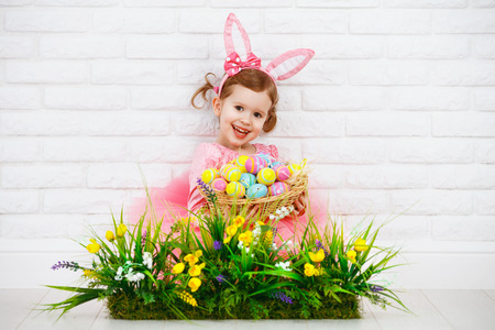 white eggs: Happy child girl in costume Easter bunny rabbit with ears and a basket of eggs and green grass with flowers