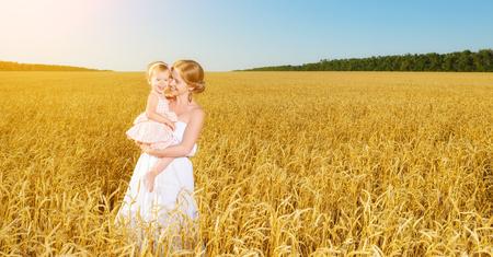 familia feliz en la naturaleza de verano. Madre e hija bebé reír, abrazar, jugar en el campo de trigo