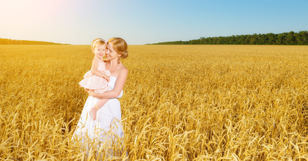 happy family in summer nature. Mother and baby daughter laugh, hug, play in the wheat field