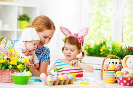 happy family mother and two children in costumes rabbit preparing for Easter, paint eggs and decorate the home