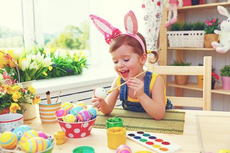 Niña feliz pinta los huevos de Pascua en el hogar