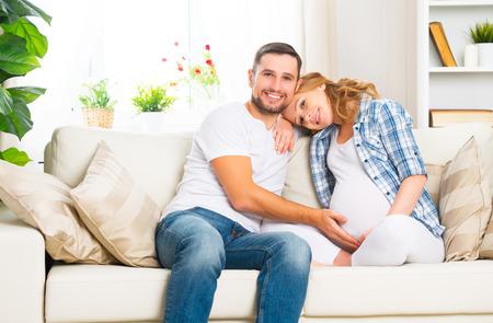 pareja en casa: familia feliz en la anticipación del nacimiento del bebé. Mujer embarazada y su marido en el sofá de casa Foto de archivo