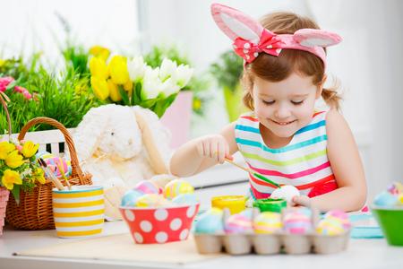 niños sonriendo: Niña feliz pinta los huevos de Pascua en el hogar Foto de archivo