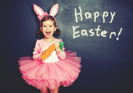 Happy Easter! child girl in costume bunny rabbit with e carrot about blackboard