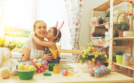 family love: happy family celebrating Easter. mother and daughter kissing at home with decorations multi colored eggs and flowers Stock Photo