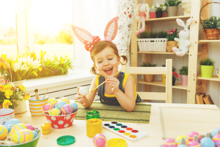 Happy child girl paints eggs for Easter at home
