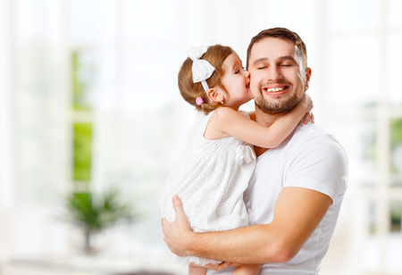 gelukkig gezin en vaderdag. kind dochter kussen en knuffelen vader