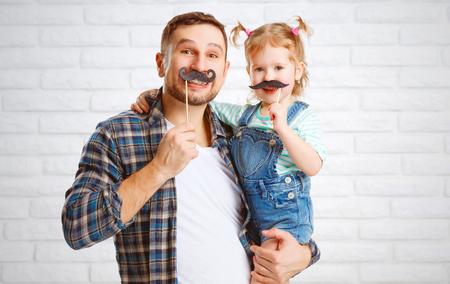 padres e hijos felices: divertido padre de familia y su hija niño con un bigote Foto de archivo