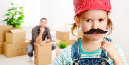 cardboard box: family moving home and renovation. funny child girl with a mustache foreman and father