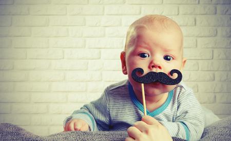 bebé divertido con un bigote en el fondo de la pared de ladrillo