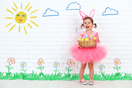 persona feliz: Concepto de Pascua. Niña feliz en un traje de conejo de conejito con los oídos y una cesta de huevos