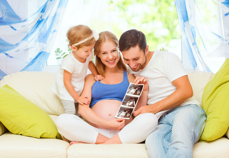 Happy family waiting for baby looking ultrasound pregnant mom, dad, child daughter Stok Fotoğraf