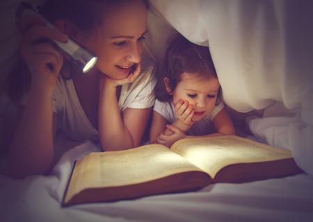 Rodzina czytania przed snem. Mama i córka dziecko czyta książkę z latarką pod kołdrą w łóżku