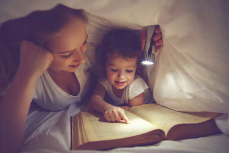 bedtime: Family reading bedtime. Mom and child daughter reading a book with a flashlight under the blanket in bed