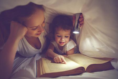 Lectura familiar antes de acostarse. Madre e hija hijo leyendo un libro con una linterna debajo de la manta en la cama