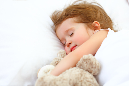child little girl sleeps in the bed with a toy teddy bear Stockfoto