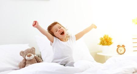 morning awakening little child girl in bed