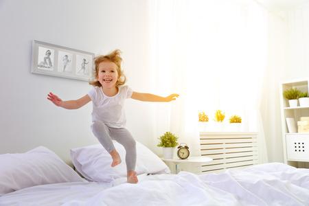 glückliches Kind Mädchen, das Spaß springt und spielt Bett Lizenzfreie Bilder