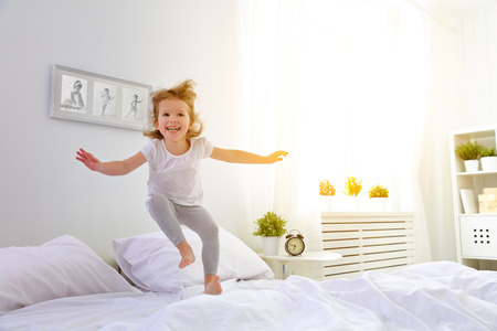 female kid: happy child girl having fun jumps and plays bed