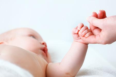 massage enfant: concept de l'amour parental. nouveau-né main tenant un doigt de la mère