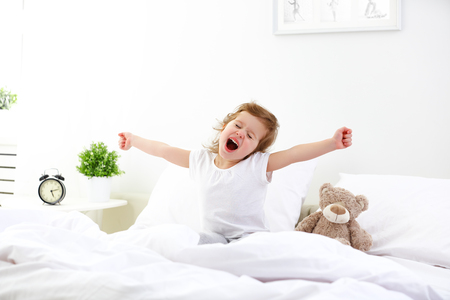 's ochtends ontwaken klein kind meisje in bed