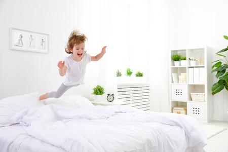 niña feliz niño que se divierte salta y juega la cama