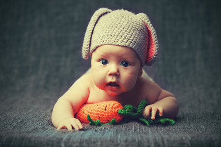 happy baby child in costume a rabbit bunny with carrot on a grey background