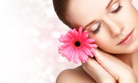 ピンクの花ガーベラを持つ少女の肖像画を自然の美しさ