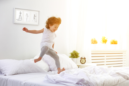white sheet: happy child girl having fun jumps and plays bed