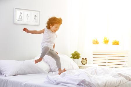 cama: niña feliz niño que se divierte salta y juega la cama