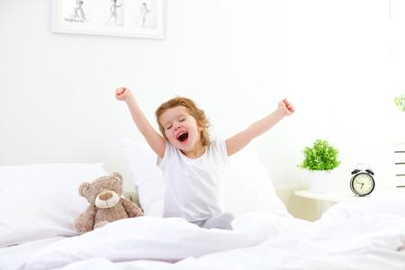 朝のベッドの子の少女を目覚め 写真素材