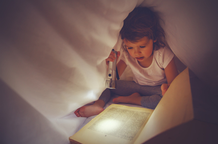 blanket: child girl reading a book in the dark, under covers in bed with light of flashlight