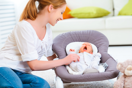 parents and baby: happy family. mother plays and laughs with her newborn baby Stock Photo