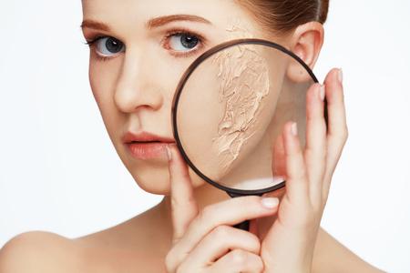 concetto di ringiovanimento e la cura della pelle. volto di una bella ragazza con una pelle problema e lente d'ingrandimento Archivio Fotografico