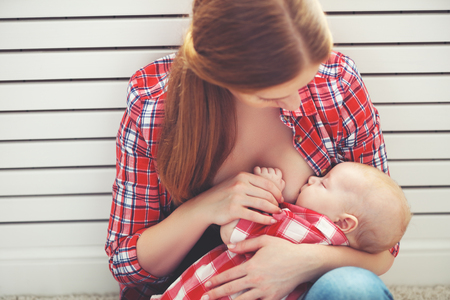 woman drinking milk: breastfeeding. mother breast feeding her baby toddler
