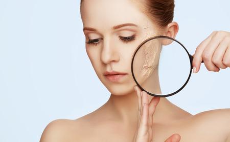 concept van de verjonging en huidverzorging. gezicht van een mooi meisje met een onzuivere huid en vergrootglas Stockfoto