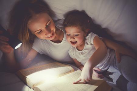 Familie lezen voor het slapengaan. Moeder en kind dochter het lezen van een boek met een zaklamp onder de deken in bed