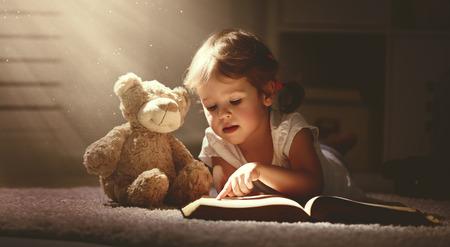 Kind kleines Mädchen, das ein magisches Buch in der Dunkelheit nach Hause mit einem Spielzeug Teddybär Lesen