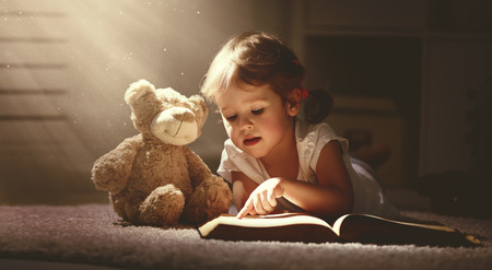 ni�as peque�as: ni�a ni�o leyendo un libro m�gico en el hogar oscuro con un oso de peluche de juguete Foto de archivo