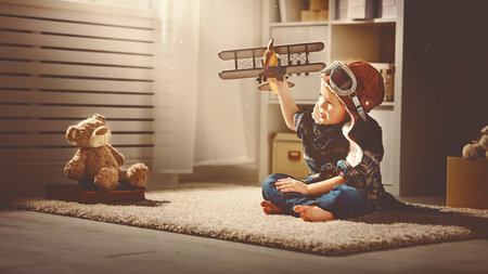 teddies: concept of childrens dreams and travels.  pilot aviator child with a toy airplane plays at home in his room