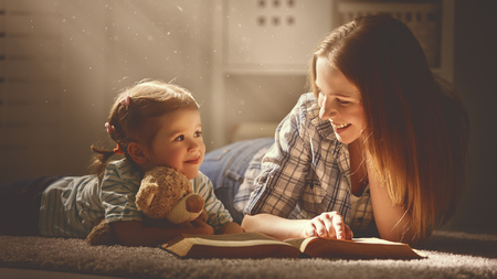 mother: happy family mother and daughter read a book in the evening at home
