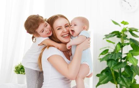 glückliche Familie Mutter und zwei Kinder, Sohn und Tochter im Bett spielen Lizenzfreie Bilder