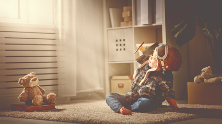 pilot light: concept of childrens dreams and travels.  pilot aviator child with a toy airplane plays at home in his room