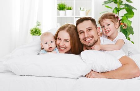 幸せな家族の母、父と自宅のベッドで 2 人の子供