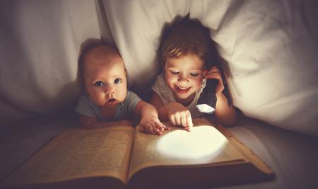 子供たちの兄と妹のベッドで毛布の下 aflashlight と本を読んでください。