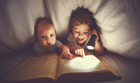 children brother and sister read a book with aflashlight under blanket in bed