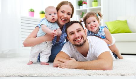 gelukkige familie moeder, vader en twee kinderen spelen en knuffelen thuis op de vloer