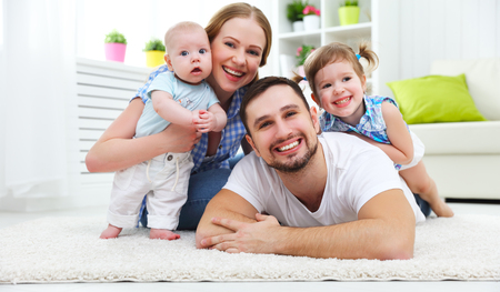positive: happy family mother, father and two children playing and cuddling at home on floor